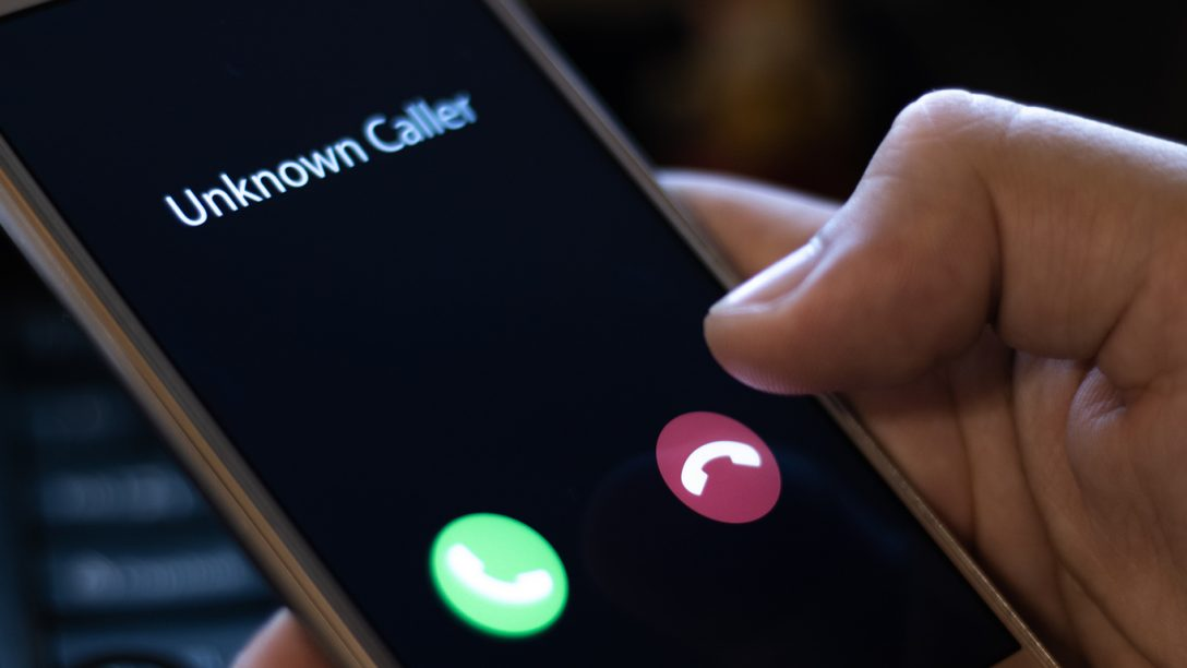 Unknown caller. A man holds a phone in his hand and thinks to end the call. Incoming from an unknown number at night. Incognito or anonymous