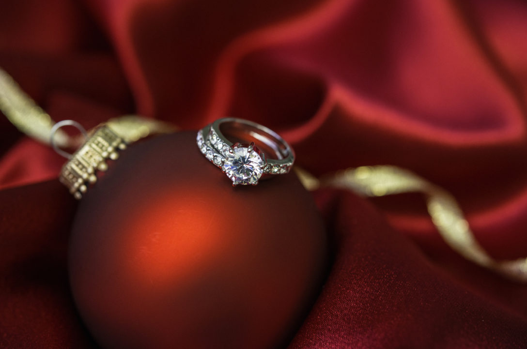 Christmas bauble with wedding and engagement rings in red satin